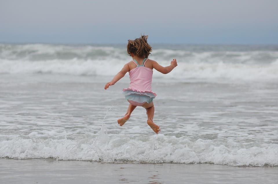 Hoppande flicka på strand
